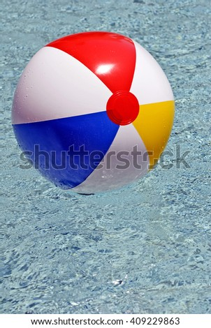 Sun shining down of colorful beach ball floating in swimming pool/ Sun Shining Down On Beach Ball Floating In Pool - stock photo