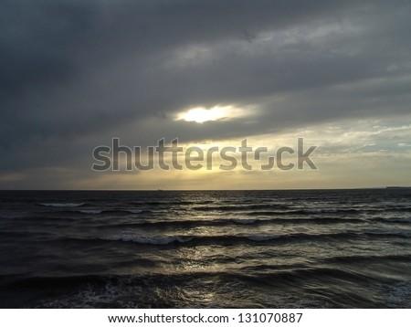 sun shining through clouds over ocean at sunset karachi pakistan - stock photo