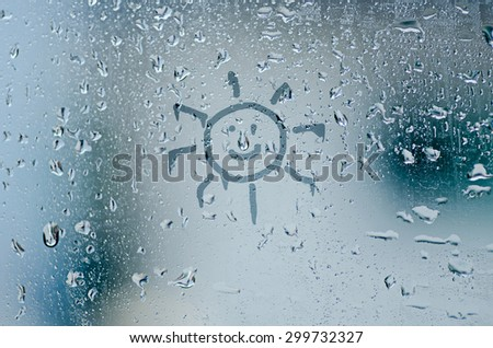 sun sign on natural water drops on glass window background - stock photo