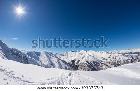 Sun star glowing over snowcapped mountain range and high mountain peaks in the italian alpine arc, in a bright sunny day of winter. Candid snowy slope in the foreground. - stock photo