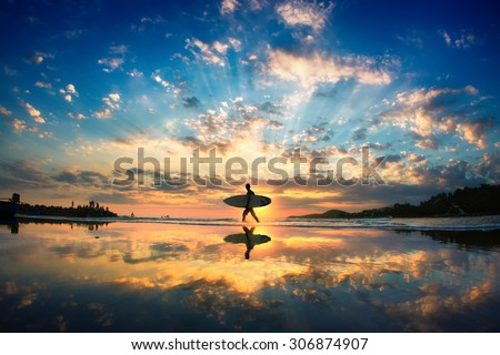 Sun surfer. A man is walking with a surf in his hands across the sea shore.  - stock photo