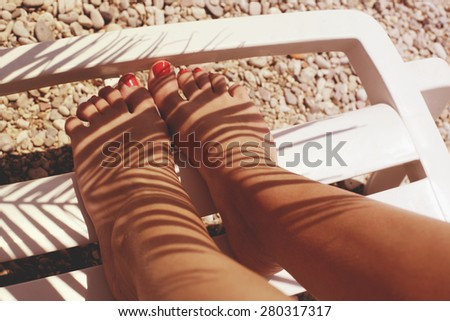 Sun tanned female legs under palm shadow - stock photo