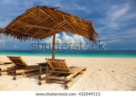 Sun umbrella and beach beds on tropical beach.  - stock photo