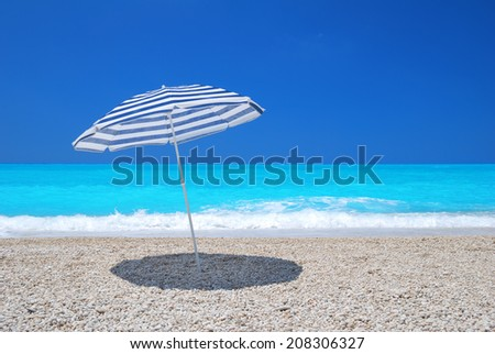 Sun umbrella on a pebble beach with turquoise sea and sky - stock photo