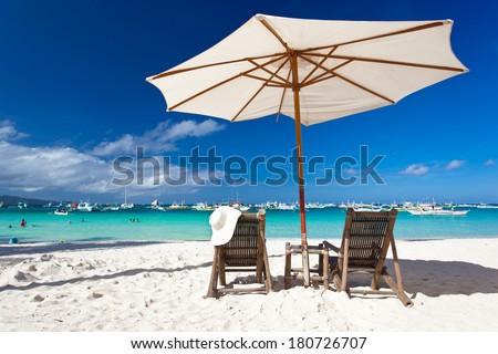 Sun umbrella with chair longue on tropical beach  - stock photo