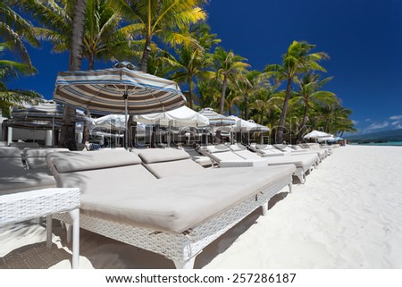Sun umbrellas and beach beds on tropical coastline, Philippines, Boracay