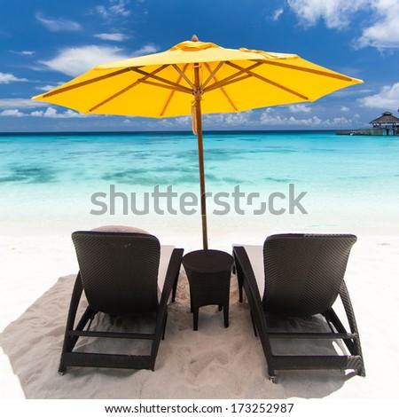 Sun umbrellas and chairs on caribbean beach - stock photo