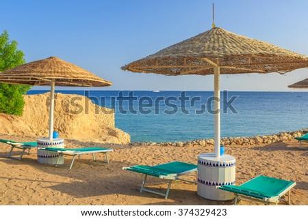 Sun umbrellas and empty deckchairs on the shore sand beach  - stock photo