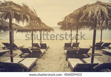 Sun umbrellas and sunbeds on beautiful sandy beach. Retro filter. - stock photo
