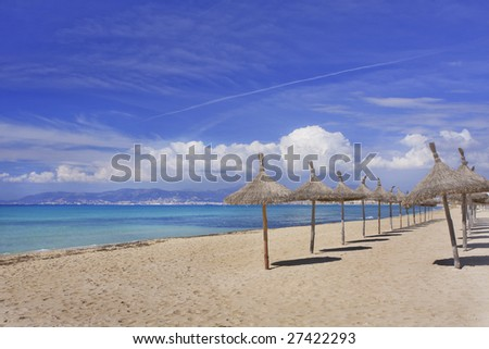 Sun umbrellas on the beach in Mallorca Spain - stock photo