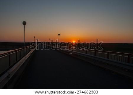 Sun under copper color sky suggests calm and solitude - stock photo