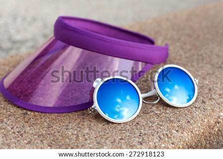 Sun visor and sunglasses beside a swimming pool  - stock photo