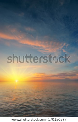 sun with rays extends beyond the sea horizon - stock photo