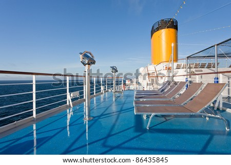 sunbath chairs on upper deck of cruise liner - stock photo