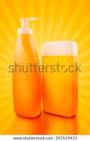 Sunbath oil or sunscreen bottles. Blank yellow plastic bottles. - stock photo
