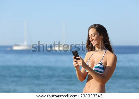 Sunbather girl wearing bikini using a smart phone on summer holidays on the beach - stock photo