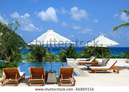 Sunbathing Beds along the swimming pool by the beach - stock photo