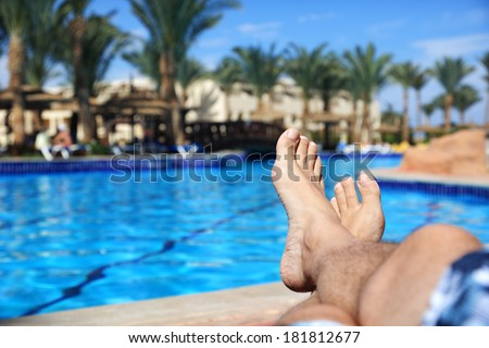 Sunbathing by the hotel tourist resort swimming pool, mans legs lying down on a sunlounger looking over the water - stock photo