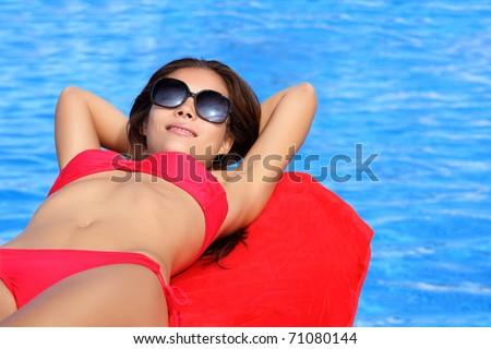 Sunbathing woman by pool on summer holidays. Natural beautiful multiracial Asian Caucasian young female model in bikini - stock photo