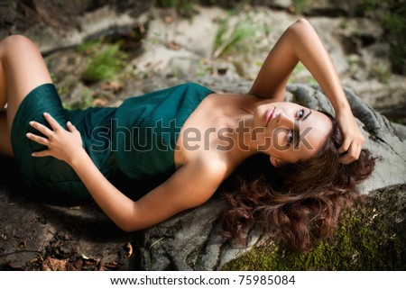 Sunbathing. Woman enjoying the sun while lying on a stone - stock photo