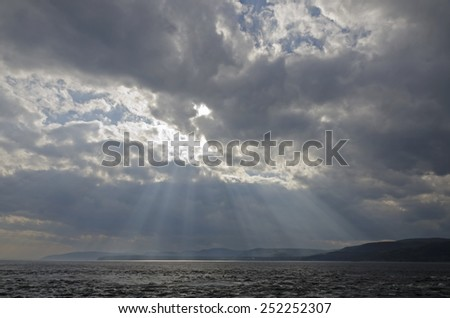 Sunbeam on dark sky above the water of St. Lawrence river - stock photo