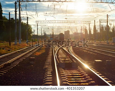 Sunbeam reflected in a railroad track  at sunset - stock photo