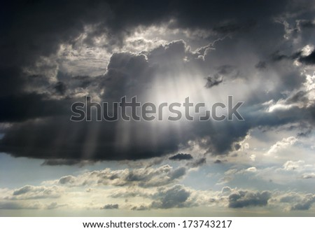 Sunbeams coming out from threatening thunderstorm cloud. - stock photo
