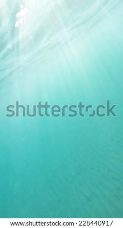 Sunbeams in deep blue ocean - stock photo
