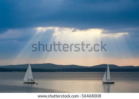 Sunbeams in the cloudy sky with two yachts in the foreground - stock photo