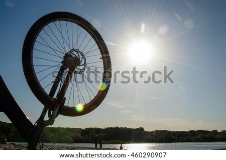 Sunbeams in the wheel of the mountain bike and the silhouettes of people relaxing on the river at sunset. - stock photo