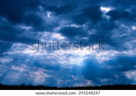 sunbeams through dark clouds - stock photo