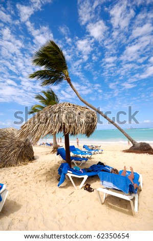 Sunbeds and parasol on an exotic beach. Dominican Republic, Punta Cana. - stock photo