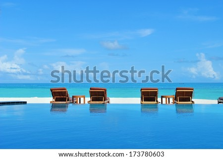 Sunbeds beside swimming pool in maldives beach resorts   - stock photo