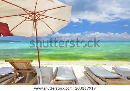 Sunbeds on the tropical white sandy beach -- Vacation and Tourism concept  - stock photo