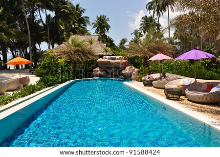 Sunbeds with colorful umbrellas beside a pool - stock photo