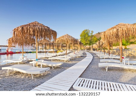 Sunbeds with parasols at Mirabello Bay on Crete, Greece - stock photo