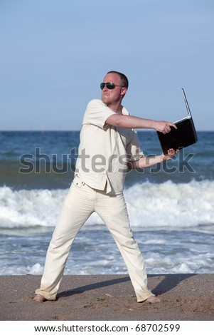 Sunburned businessman at the beach throwing his laptop. Concept of protesting against work on vacation - stock photo