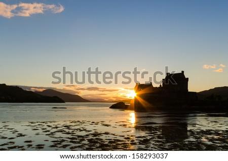 Sunburst on Eilean Donan castle / Eilean Donan the iconic Scottish castle at dusk - stock photo