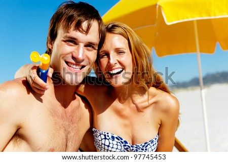 suncare couple on a summer beach vacation have good skincare with high spf sunblock - stock photo
