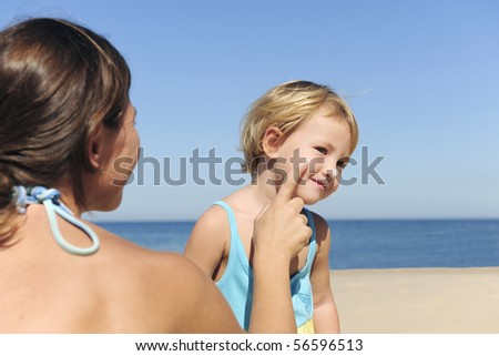 Suncare on the beach: Mother applying suntan lotion to her daughter - stock photo