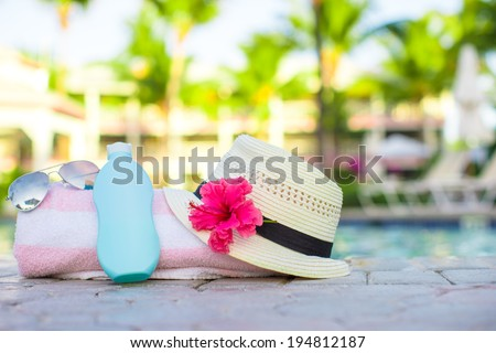 Suncream, hat, sunglasses, flower and tower near swimming pool - stock photo