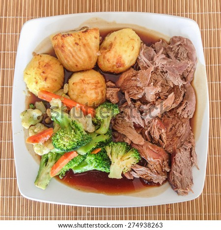 Sunday lunch meal of roast lamb, roast potatoes, gravy and vegatables on a white plate from above. - stock photo