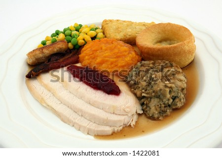 Sunday roast - Thanksgiving dinner, consisting of chicken or turkey, cranberry sauce, pumpkin, stuffing, yorkshire pudding and gravy. Macro, close up - stock photo