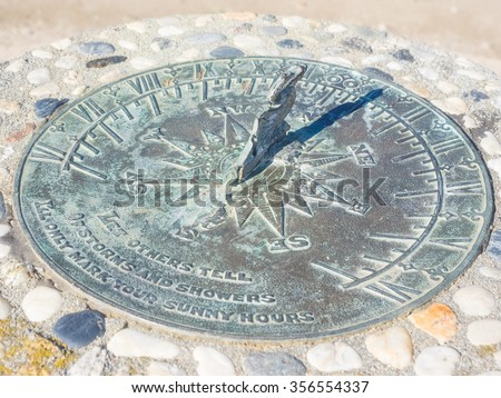 Sundial is a device that tells the time of day by the apparent position of the Sun in the sky.  - stock photo
