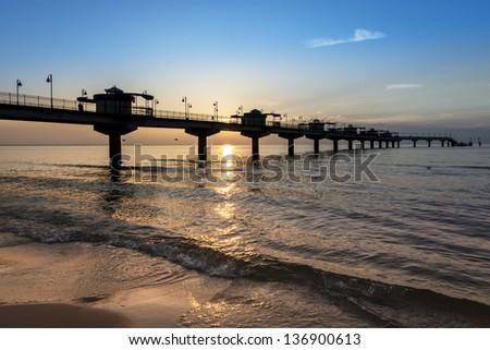 Sundown over pier in Miedzyzdroje, Poland, baltic sea - stock photo