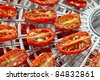 sundried cherry tomatoes on food dehydrator tray, shallow dof - stock photo