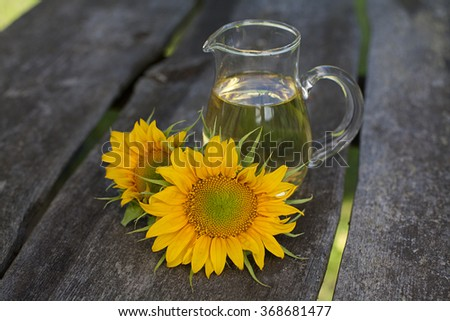 sunflower oil on garden table - stock photo