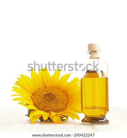 Sunflower oil with flower on the wooden table and white background. - stock photo