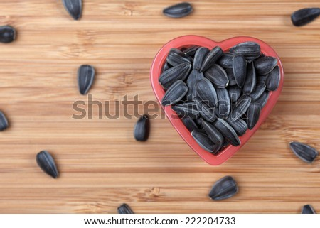 Sunflower seed in a heart bowl. Close-up. - stock photo