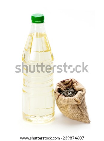 Sunflower seed in jute sack with oil bottle on white background - stock photo